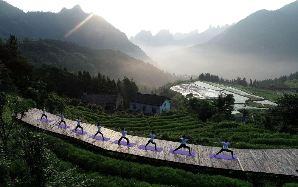 عشاق اليوغا يمارسون اليوغا في قرية تشيكي الجبلية في زانغجياجي بمقاطعة هونان وسط الصين، 20 يونيو/ حزيران 2019 - يذكر أن 21 يونيو/ حزيران هو يوم اليوغا العالمي