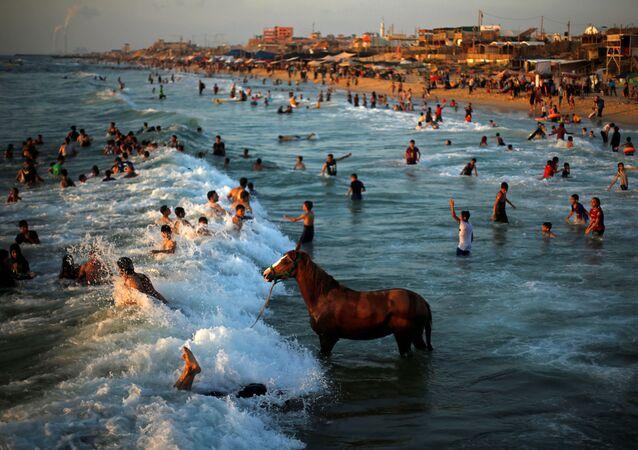 السباحة في البحر الأبيض المتوسط في يوم حار في شمال قطاع غزة في 18 يونيو/ حزيران 2019