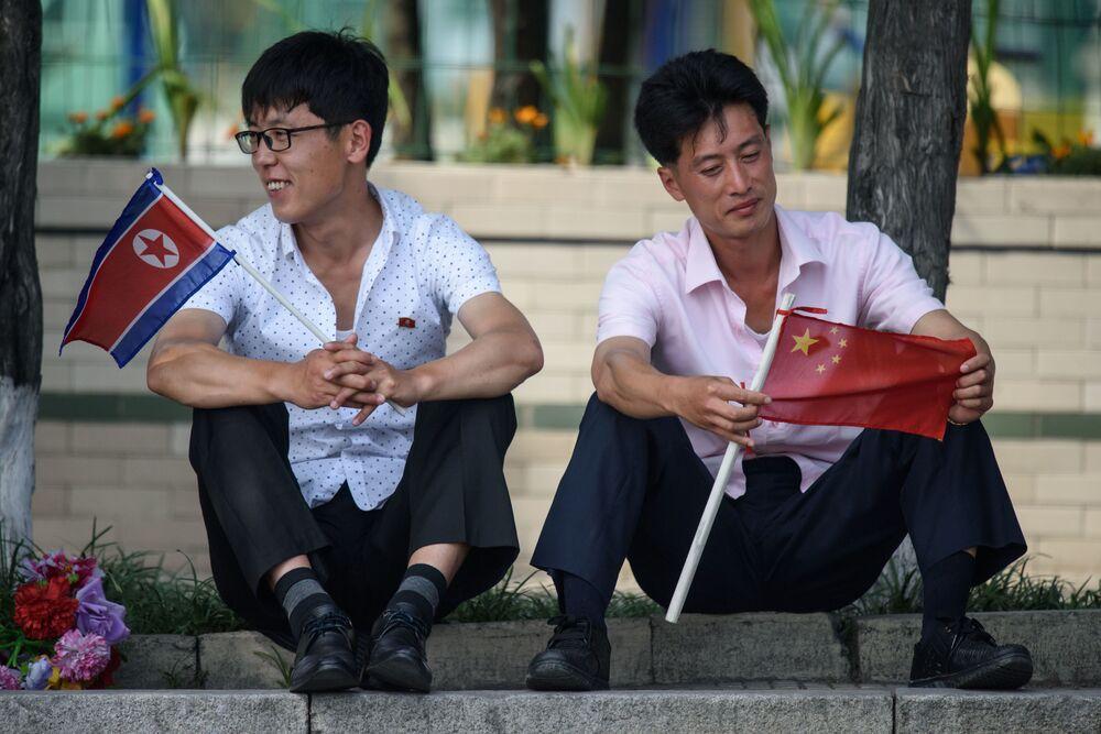 رجلان في شوارع بيونغ يانغ، خلال مراسم استقبال الرئيس الصيني شي جين بينغ، وهي الزيارة الأولى من نوعها منذ 11 عاما إلى كوريا الشمالية 20 يونيو/ حزيران 2019