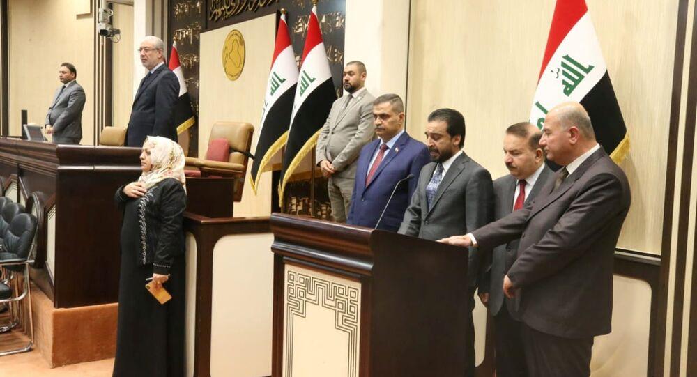 رئيس البرلمان العراقي محمد الحلبوسي يقف مع الوزراء المفوضين حديثاً خلال مراسم أداء اليمين في مقر البرلمان في بغداد