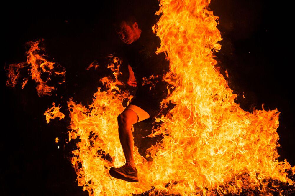 رجل يقفز فوق النار في الاحتفال بليلة القديس خوان في إسبانيا