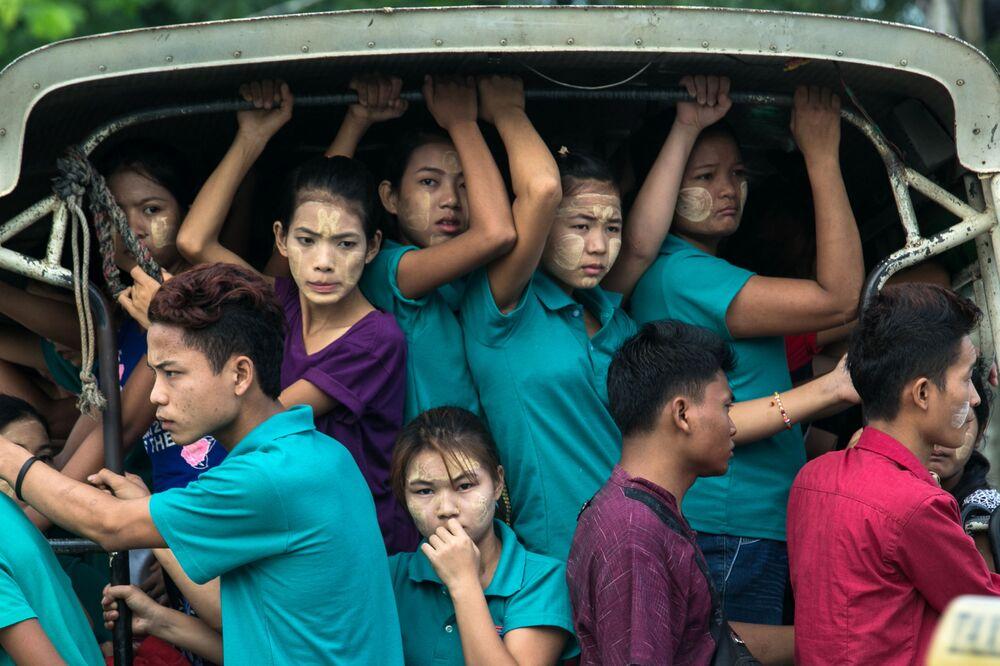 عمال يركبون الجزء الخلفي من مركبة في طريقهم إلى المصانع في بلدة هلاينغ ثاريار في ضواحي يانغون في ميانمار 26 يونيو/ حزيران 2019