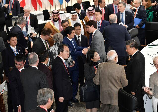 رئيس الوزراء الياباني شينزو آبي يصافح رئيس الوزراء الكندي جاستن ترودو خلال الجلسة الختامية لقمة قادة مجموعة العشرين في أوساكا