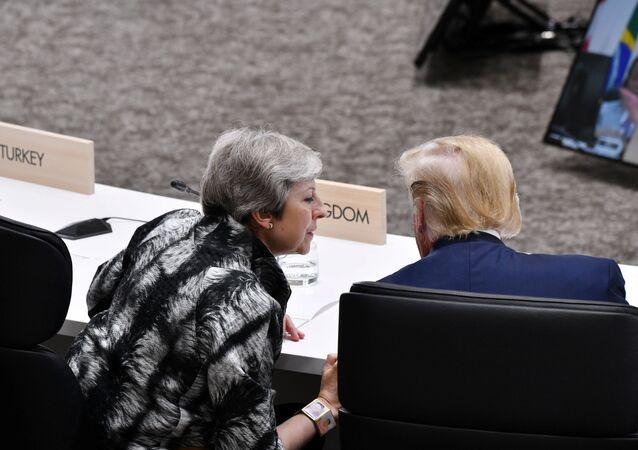 رئيسة وزراء بريطانيا تيريزا ماي تتحدث مع الرئيس الأمريكي دونالد ترامب خلال الجلسة الختامية لقمة قادة مجموعة العشرين في أوساكا