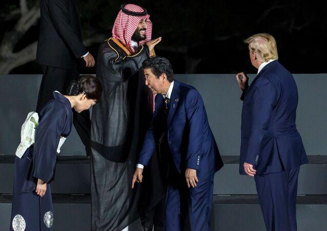 رئيس الوزراء الياباني شينزو آبي يتفقد موقعه مع زوجته آكي آبي حيث يتحدث ولي العهد السعودي الأمير محمد بن سلمان إلى الرئيس الأمريكي دونالد ترامب أثناء جلسة تصوير جماعية أمام قلعة أوساكا في قمة مجموعة العشرين في أوساكا باليابان