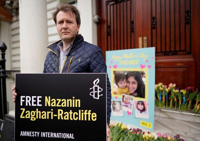 ريتشارد راتكليف زوج البريطانية الإيرانية نازانين زغاري راتكليف يلتقط صورة فوتوغرافية بعد تسليمه بطاقة عيد الأم والزهور إلى السفارة الإيرانية في لندن