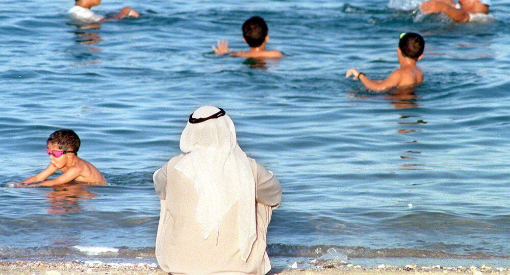 مواطن كويتي يراقب الأطفال وهم يسبحون في البحر بالكويت بالتزامن مع ارتفاع درجات الحرارة في البلاد