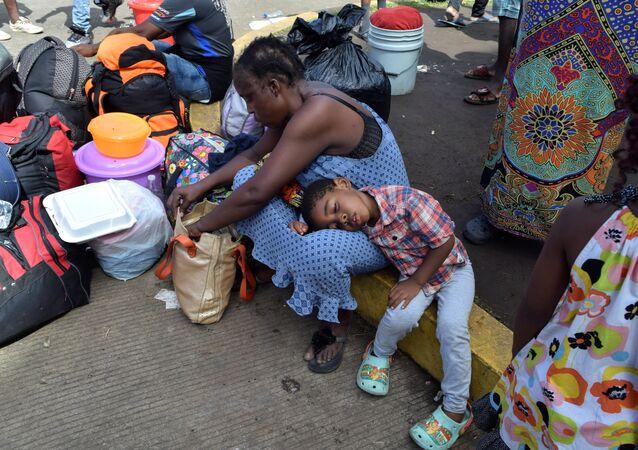 مهاجرون من الكاميرون يستريحون أثناء انتظارهم مع مهاجرين آخرين من أفريقيا وهايتي لدخول مركز احتجاز المهاجرين