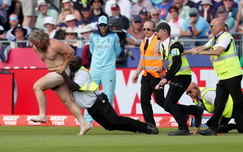 عناصر الأمن يحاولون القبض على رجل عاري خرج إلى أرض الملعب خلال مباراة كريكيت بين فريقي إنجلترا ونيوزيلندا، بريطانيا 3 يوليو/ تموز 2019