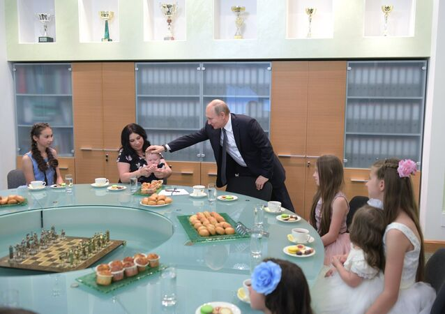 الرئيس الروسي فلاديمير بوتين يطعم طفلا