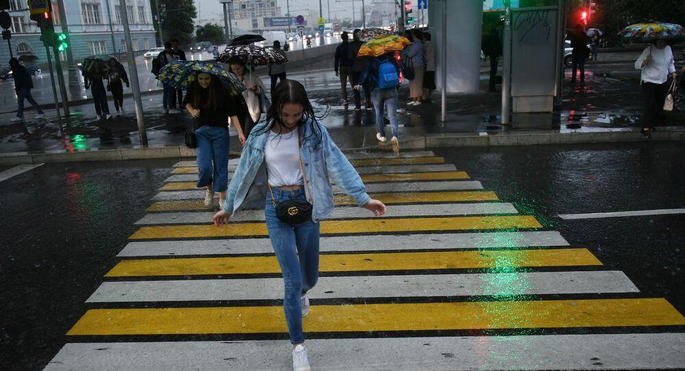 فتاة على ممر الشماه خلال هطول أمطار غزيرة في موسكو. أفاد مركز الأرصاد الجوية سابقا أن الصيف الحقيقي قد تعود في شهر أغسطس/ آب القادم (ربما في نهايته)!