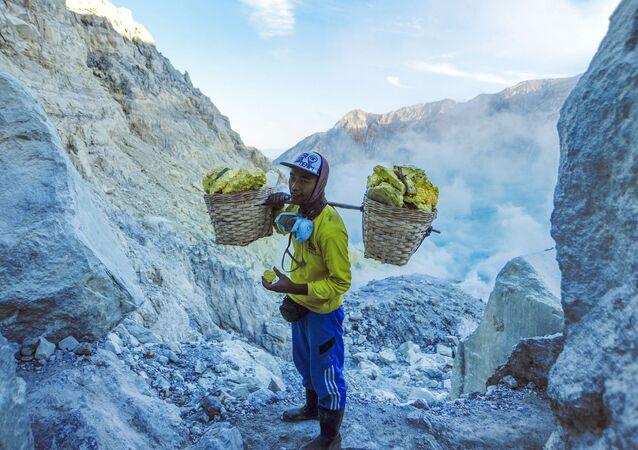 عامل منجم ينقل سلال الكبريت الصلب من مقلع يقع على البركان النشط كواه آيجن (Kawah Ijen) في إندونيسيا. يسود الفقر في المنطقة، والعمال ليس لديهم ملابس خاصة لهذه الوظيفة، ومتوسط الأجور، يتراوح بين 7-8 دولارات في اليوم. يقوم كل عامل منجم بنقل 75-90 كغم من الكبريت من المنجم في رحلة واحدة.