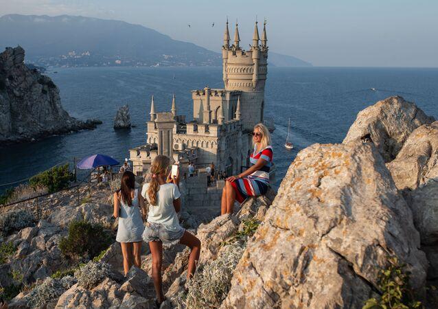 سياح يلتقطون صورا على خلفية قلعة السنونو خارج يالطا، القرم، روسيا