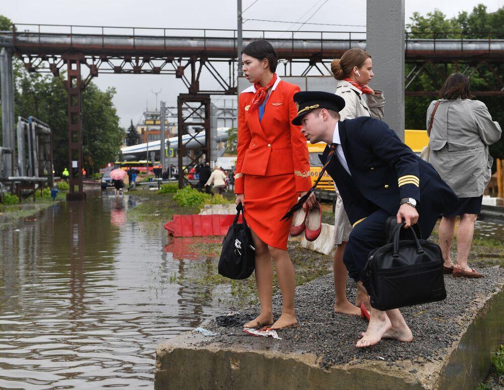 موظفو شركة خطوط الطيران الجوي آيروفلوت في شارع غمرته المياه بالقرب من مطار شيريميتيفو في ضواحي موسكو