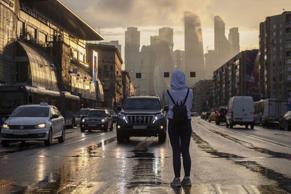 فتاة تتوقف على ممر للمشاة في حي كوتوزوفسكي بروسبيكت لتلتقط صورة لمجمع موسكو سيتي وسط موسكو بعد سقوط أمطار غزيرة.