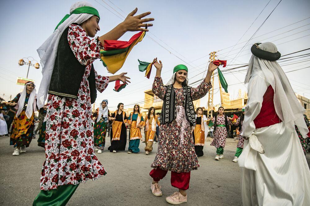 أكراد سوريون يرتدون ملابس تقليدية يرقصون الدبكة في أحد شوارع مدينة الرميلان في شرق محافظة الحسكة، شمال سوريا، 27 يوليو/ تموز 2019.