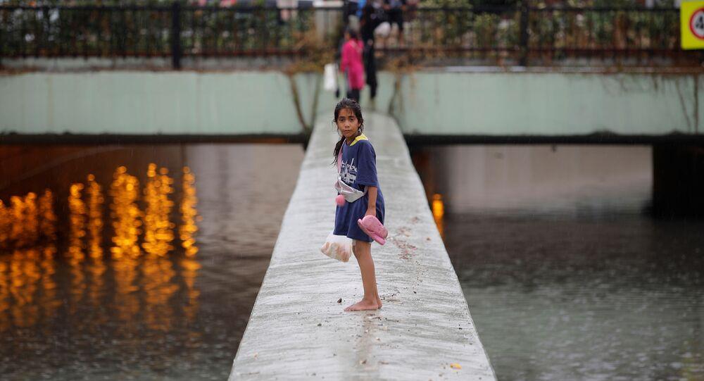 فتاة حافية القدمين تقف وسط شارع عائم نتيجة الفيضانات التي اجتاحت اسطنبول، تركيا، 17 أغسطس/آب 2019