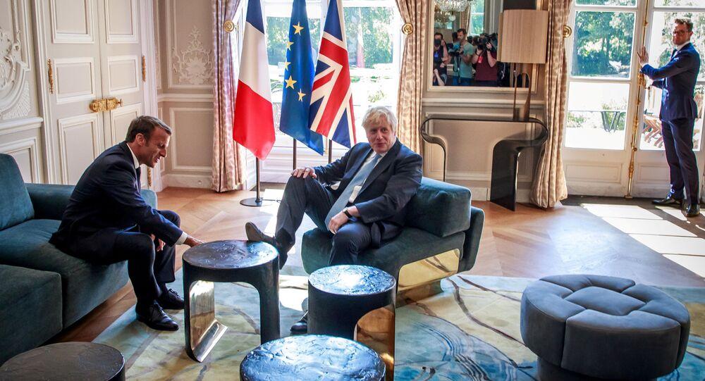 رئيس وزراء بريطانيا بوريس جونسون يضع قدمه على طاولة أمام الرئيس الفرنسي إيمانويل ماكرون بداخل قصر الإليزيه بالعاصمة الفرنسية باريس، 22 أغسطس/آب 2019