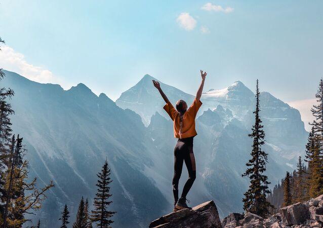 قتاة تقف على خلفية جبال في كندا