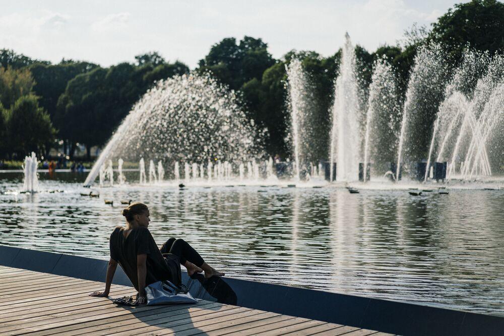 فتاة جالسة بالقرب من نافورة مياه في حديقة غوركي في موسكو، 10 سبتمبر 2019