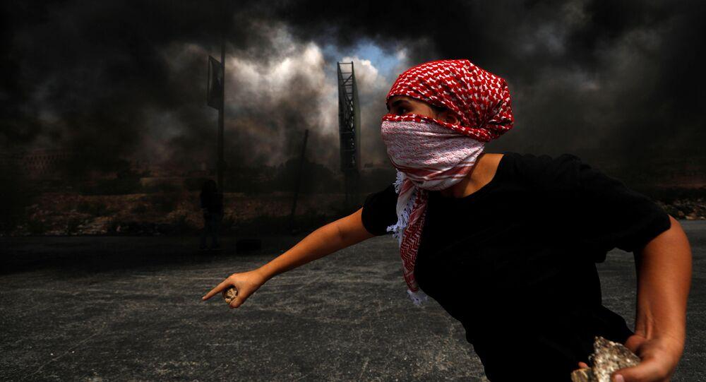 أحد المتظاهرين الفلسطينيين يقذف الحجارة بالقرب من مستوطنة يهودية في بيت إيل، الأراضي المحتلة بالضفة الغربية، 9 سبتمبر 2019