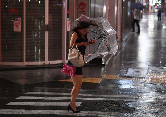 امرأة تقف وسط الرياح القوية في طوكيو، اليابان 8 سبتمبر 2019