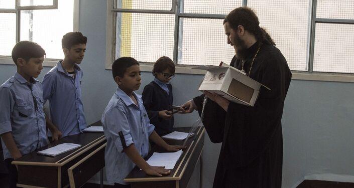 الراهب يرموغين (كورتشوكوف) في أحد الفصول في مدرسة الشهيد عدنان كولكي في حي برزة بدمشق، سوريا