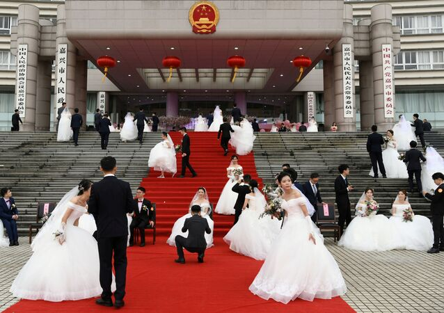 الأزواج يحضرون في زفاف جماعي في مبنى الحكومة البلدية بالمدينة قبيل الذكرى الـ70 بمناسبة تأسيس جمهورية الصين الشعبية في جياشينغ بمقاطعة تشجيانغ الصين 22 سبتمبر 2019
