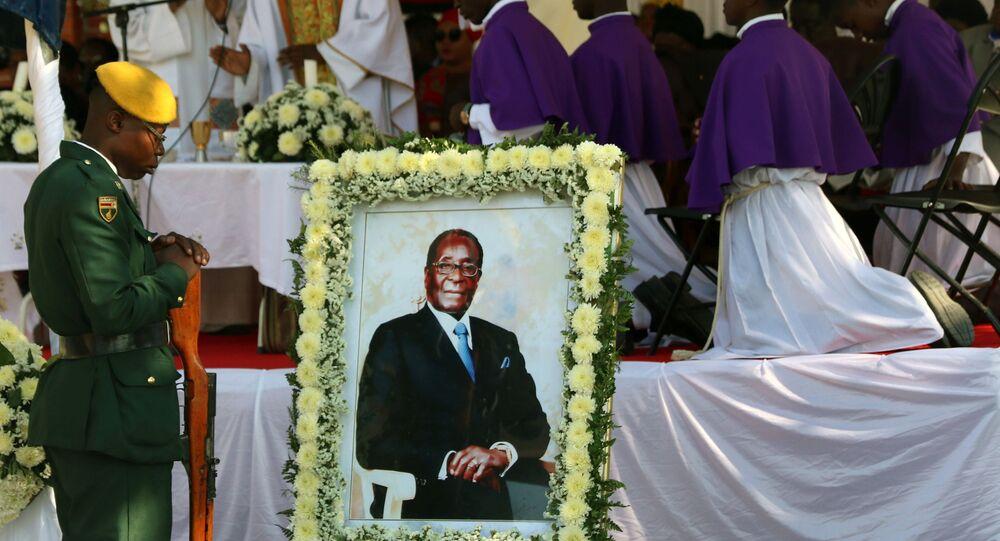 جنود يقفون بجانب صورة لرئيس زيمبابوي السابق روبرت موغابي قبل دفن جثمانه في قريته الريفية في كوتاما، 28 سبتمبر/أيلول 2019