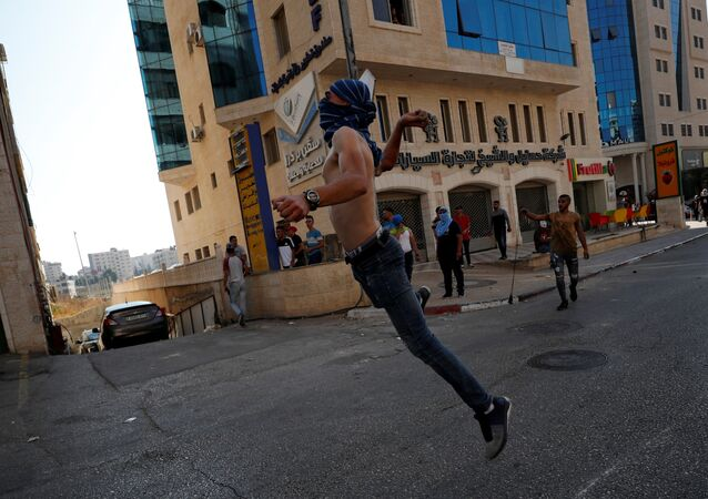 متظاهر يقذف الحجارة على القوات الإسرائيلية خلال مظاهرة لإظهار التضامن مع السجناء الفلسطينيين المحتجزين في السجون الإسرائيلية، بالقرب من مستوطنة بيت إيل في الضفة الغربية، 1 أكتوبر 2019