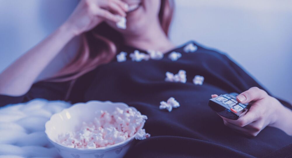 فتاة مستلقية تشاهد التلفاز وتأكل البوشار