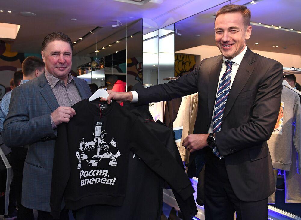 لاعب الهوكي الروسي ألكيسي كاساتونوف (يسار) ونائب وزير الصناعة والتجارة الروسي فيكتور يفتوخوف في افتتاح متجر Aizel x Team Putin في موسكو