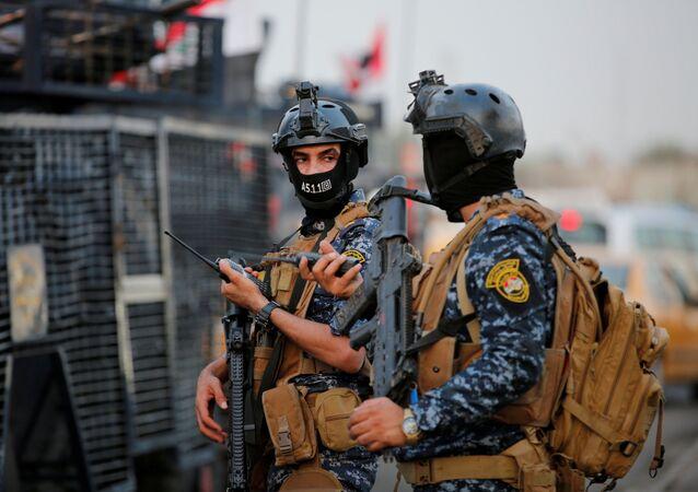 أفراد من الشرطة الفيدرالية العراقية يراقبون مركبات عسكرية في أحد شوارع بغداد، 7 أكتوبر/تشرين الأول 2019