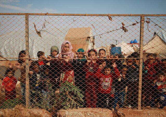 أطفال سوريون مهجرون يقفون خلف سياج مخيم كفر لوسين، في ريف إدلب الشمالي، الحدود السورية التركية، 22 أكتوبر 2019