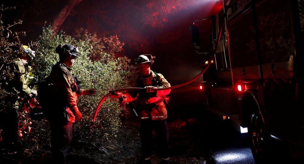رجل إطفاء يمرر خرطوما لإخماد بقعة ساخنة أثناء حريق كينكايد في هيلدسبورغ، كاليفورنيا، الولايات المتحدة، 29 أكتوبر/تشرين الأول 2019