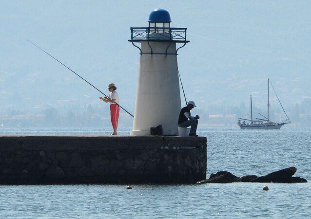 مصطافون يصطادون الأسماك بالقرب من المنارة في خليج بحر إيجه
