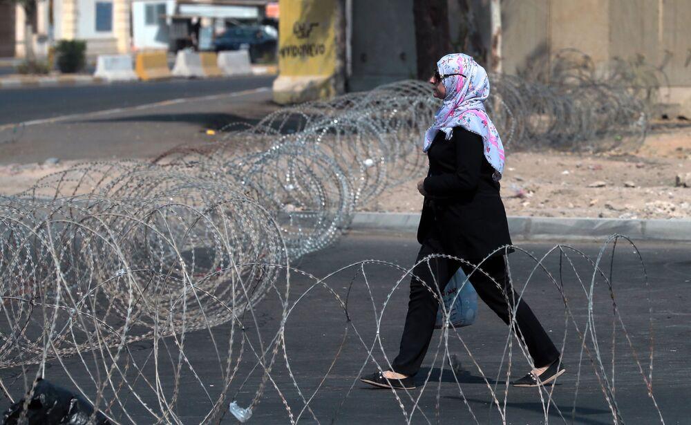 مواطنة عراقية تسير في أحد شوارع بغداد، العراق