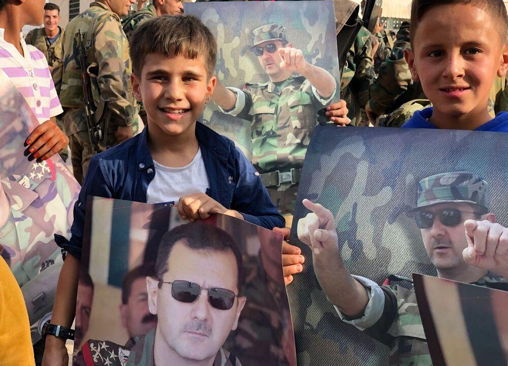 أطفال يحملون ملصقات عليها صورة للرئيس السوري بشار الأسد في مدينة منبج بعد دخول الجيش السوري إليها