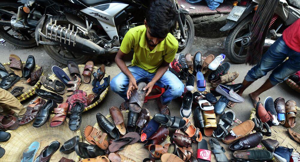 بائع أحذية في الشوارع من بنغلاديش يرتب الأحذية وهو يستعد لعرضه في دكه في 30 أكتوبر 2019