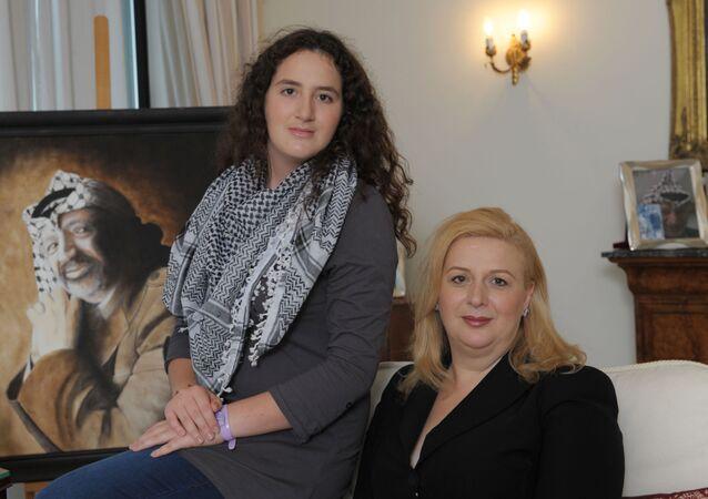 سهى عرفات وابنتها زهوة وخلفهما صورة للرئيس الفلسطيني الراحل ياسر عرفات