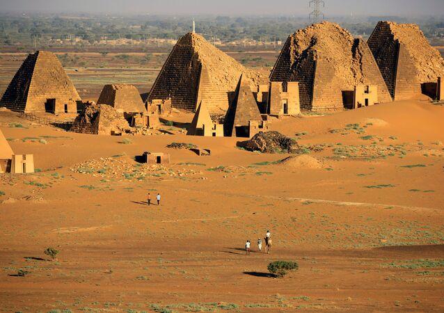 السياح يسيرون إلى المقابر الملكية لأهرامات مروي في البجراوية بولاية نهر النيل