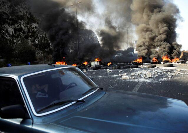 رجل ينام في سيارة بجوار إطارات محترقة على الطريق السريع خلال الاحتجاجات المستمرة المناهضة للحكومة في منطقة نهر الكلب، لبنان 13 نوفمبر 2019