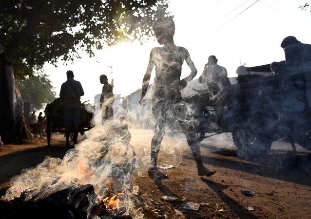 الناس يسيرون بجوار قمامة مشتعلة في كالكوتا، الهند 19 نوفمبر 2019