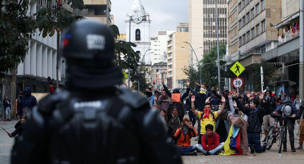 متظاهرون أمام أحد أفراد شرطة مكافحة الشغب خلال احتجاج في اليوم الثاني من الإضراب الوطني، في العاصمة الكولومبية بوغوتا