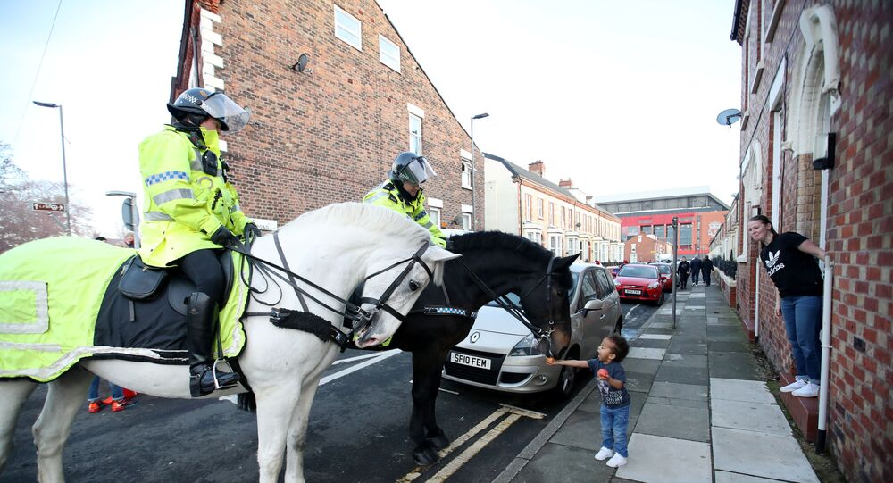 أحد أفراد الجمهور يطعم حصان شرطة خارج الملعب قبل مباراة كرة القدم - في الدوري الإنجليزي الممتاز