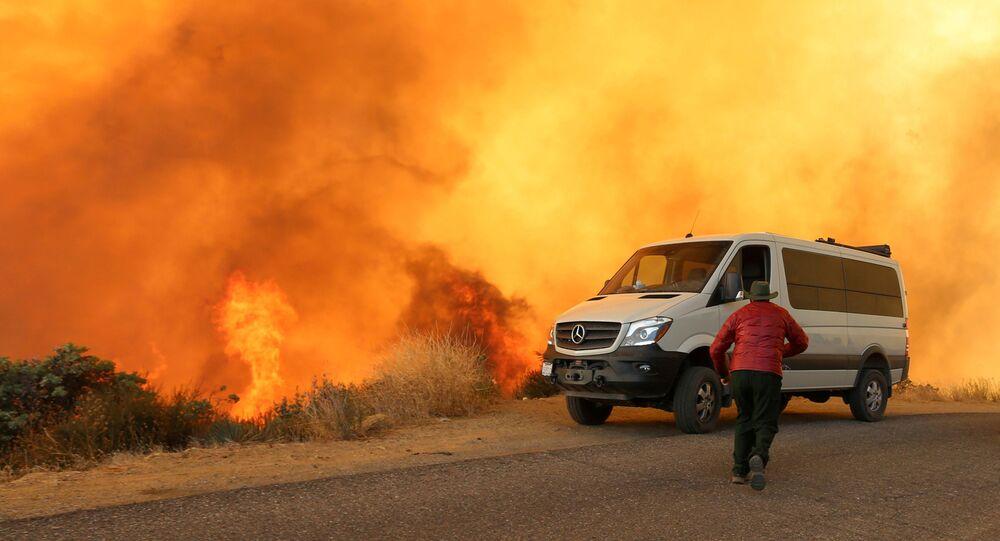 رجل يسرع إلى موقع شاحنته أثناء نشوب حرائق في كيف فاير، في هضاب سانتا باربارا، كاليفورنيا، الولايات المتحدة 26 نوفمبر 2019