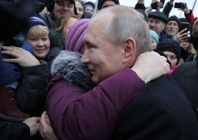 الرئيس الروسي فلاديمير بوتين يعانق مواطنة في مدينة سان بطرسبورغ بعد مراسم افتتاح نصب تذكاري للكاتب والناشط الاجاتماعي دانيال غرانين، روسيا 27 نوفمبر 2019