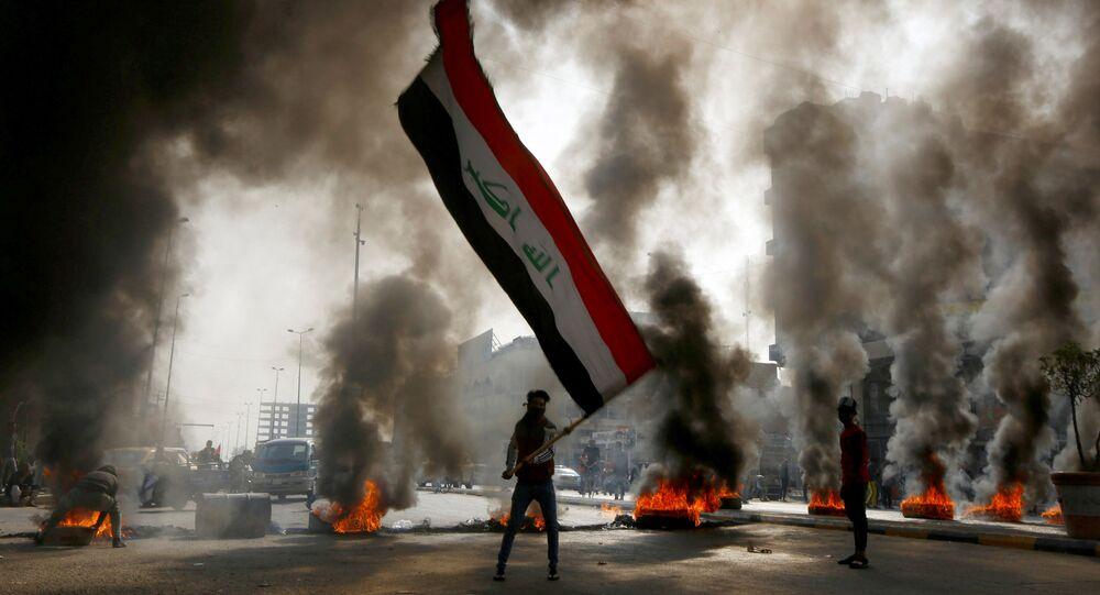 متظاهر يمسك بالعلم العراقي وسط دخان يتصاعد من الإطارات المشتعلة أثناء الاحتجاجات في النجف، العراق 26 نوفمبر 2019
