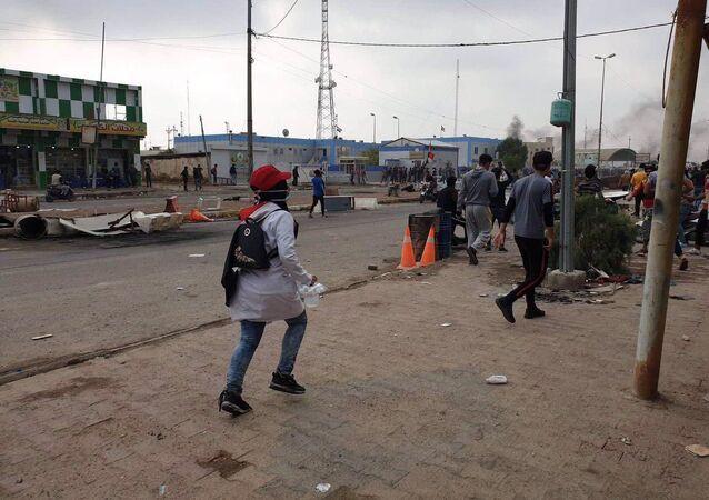 المتظاهرون يجمعون أغلفة الطلقات أثناء المظاهرات في ذي قار العراقية