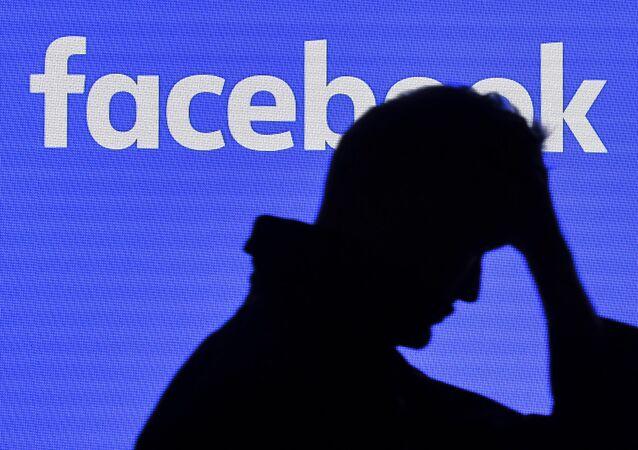 رجل يمر بجانب شاشة فيسبوك